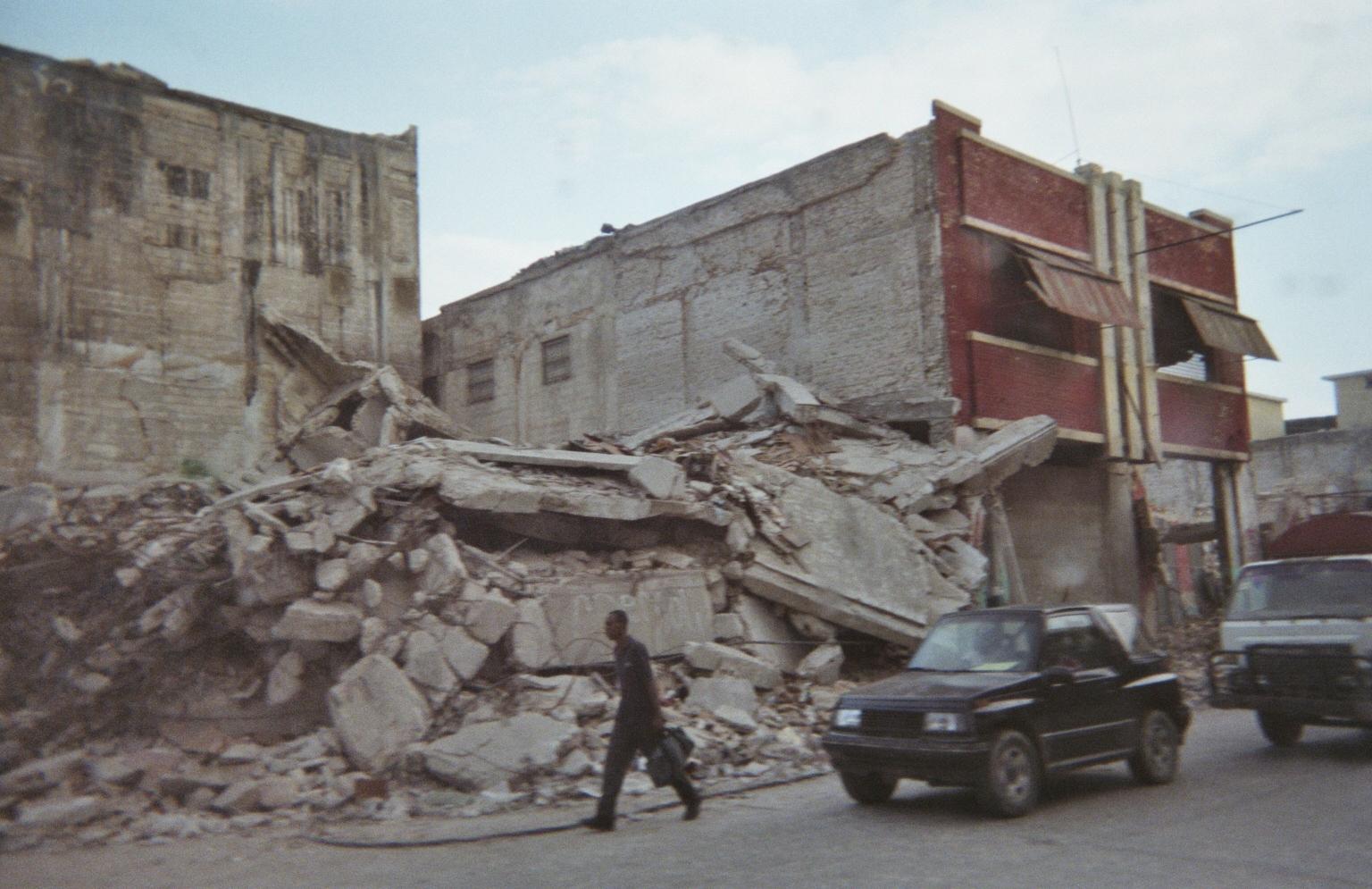 <em><strong>Commuters pass by a collapsed building, a common sight in Port-au-Prince, Haiti (Photo courtesy Dr. Hélène Rousseau)</em></strong>