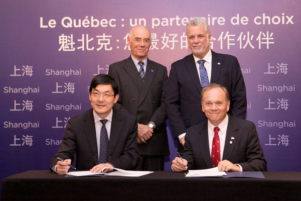 McGill's Vice-Dean of Life Sciences, Philippe Gros (seated right), and Fudan University's Wen Chen sign the agreement between the two universities as Jacques Daoust, Quebec's Minister of Economy, Innovation and Exports (standing, left) and Quebec Premier Phillippe Couillard look on. / Photo: Patrick Alleyn
