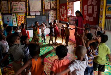 Une enseignante guide ses élèves dans un jeu impliquant le chant et le jeu de rôle dans une garderie de l'organisation BRAC dans le sous-district de Mirpur de Dhaka, la capitale. UNICEF/NYHQ2013-0364/Noorani http://www.un.org/en/events/childrenday/